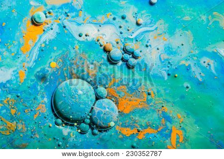 Blue paint reacts in the water creating colorful bubbles. Abstract background