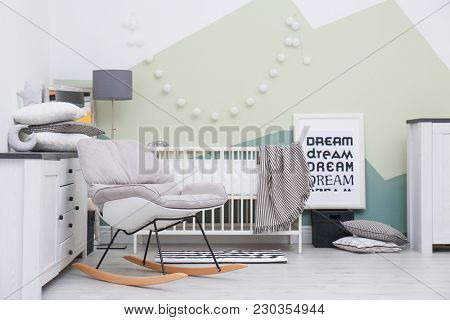 Beautiful interior of baby room with  crib and rocking chair