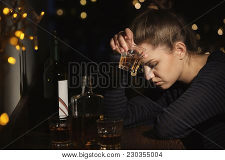 Young woman with glass of drink in bar. Alcoholism problem