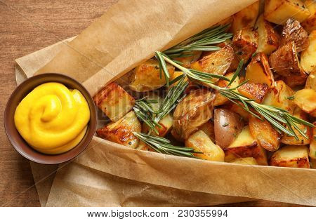 Tasty potato wedges and mustard, closeup