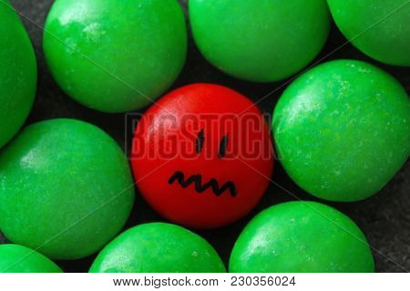 One red drop with painted sad face among green ones. Difference and uniqueness concept