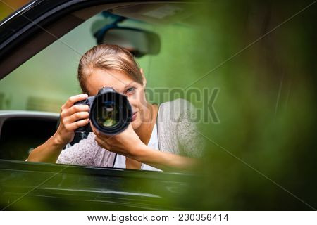 Female photographer/paparazzi taking pictures of a famous high-profile person from her car