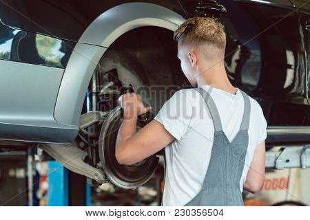 Experienced auto mechanic replacing the disk brakes of a lifted car during work in a modern automobile repair shop with professional tuning services