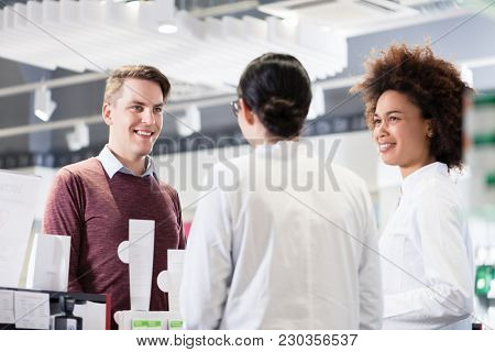 Cheerful young man and happy customer talking with two helpful female pharmacists in a contemporary drugstore with friendly employees