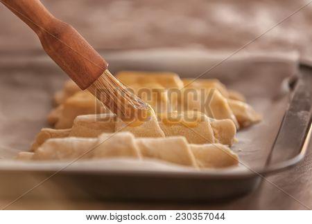 Spreading egg yolk onto croissants, closeup