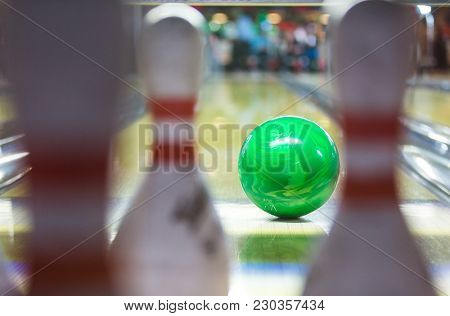 green bowling ball just in front of the 10 pins bowling cones, moments before he hits the target