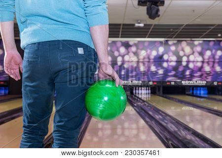 young man awaits his turn with a green bowling ball ready to throw