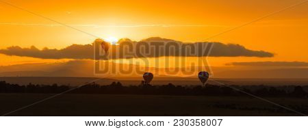 Balloon over the Masai Mara at sunrise. Three balloons drift low over the savannah at dawn. Panoramic banner in popular socila media dimensions.