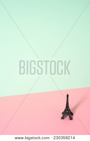 a miniature of the miniature of Eiffel Tower in a colorful pink and green background, with a large blank space on top