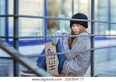 Homeless poor teenage girl holding piece of cardboard with word HELP outdoors