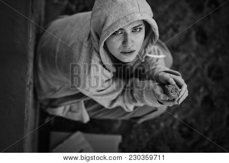 Homeless poor woman with piece of stale bread sitting outdoors