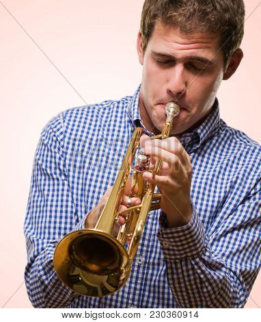 Handsome Man Blowing Trumpet against a pink background