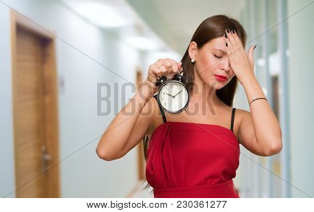 Tired Woman Holding Alarm Clock in a passage way