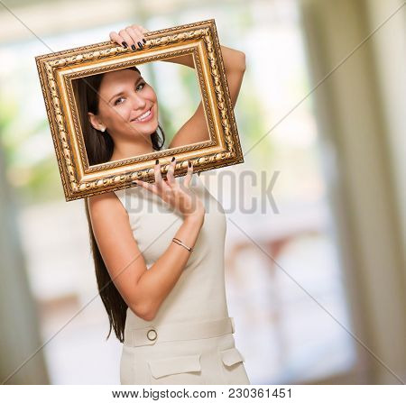 Portrait Of A Young Woman Holding Frame against an abstract background