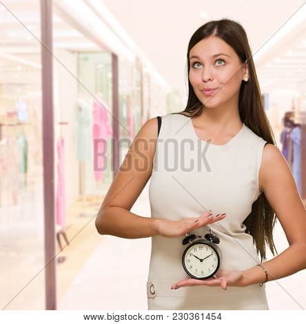 Woman Holding Alarm Clock and looking up at a mall