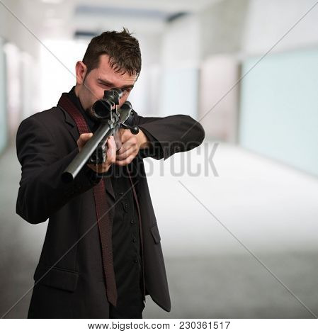 Man in suit pointing with a rifle against an abstract background
