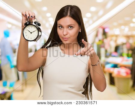 Woman Holding Alarm Clock and pointing at the mall