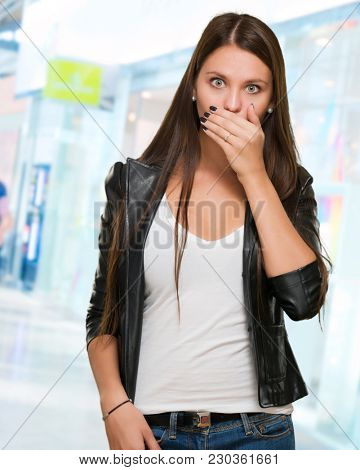 Portrait Of Surprised Young Woman against an abstract background, indoor