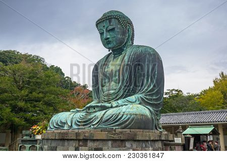 Kamakura, Japan - November 10, 2016: Tourists at statue of The Great Buddha of Kamakura, Japan. Monumental outdoor bronze statue of Amida Buddha is one of the most famous icons in Japan.