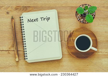 Top View Of  Next Trip Message On Notebook With Pencil ,coffee Cup And Cactus In Flowers In A Pot On