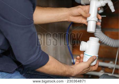 Professional plumber fixing sink, closeup