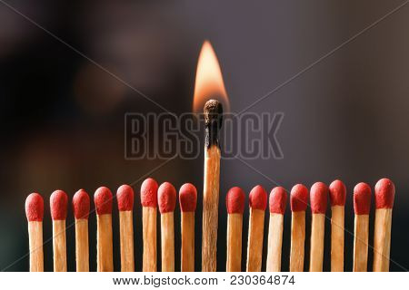 Burning match among others on black background. Difference and uniqueness concept