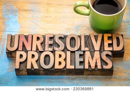 unresolved problems - word abstract in vintage letterpress printing blocks with a cup of coffee