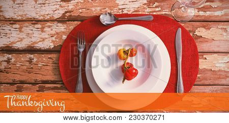 Illustration of happy thanksgiving day text greeting against overhead view of tomatoes served in plate