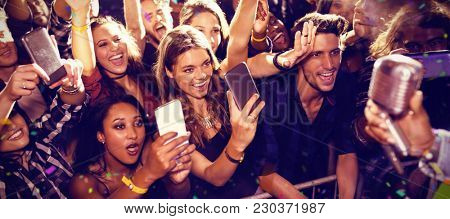 Flying colors against cheerful fans photographing performer at concert