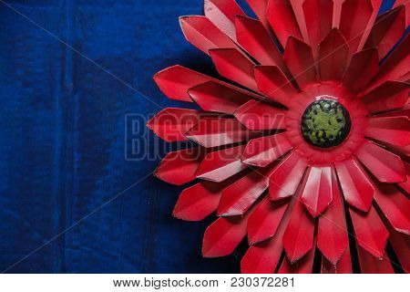 Large, Red, Metal Flower Against A Blue Background.