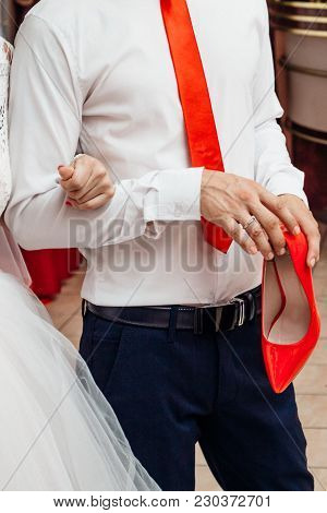The Groom In A White Shirt With A Red Tie Is Holding A Red Shoe Of The Bride
