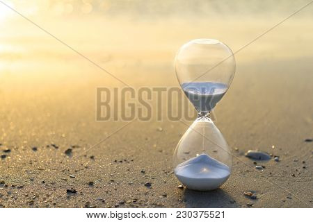 Hourglass Close Up In A Warm Golden Morning Sunlight On A Sandy Beach Starting Time For A New Day Or