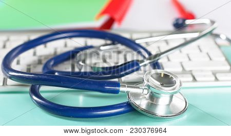 A Stethoscope Is On The Keyboard Of A Computer.