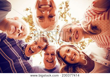 Portrait of happy multi-generation family forming a huddle in park on a sunny day