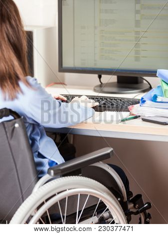 Invalid or disabled young business woman person sitting wheelchair working office desk computer poster
