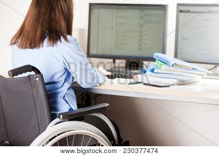Invalid or disabled young business woman person sitting wheelchair working office desk computer