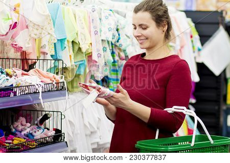 A Young Mother Buys Clothes For Her Baby In A Children's Clothing Store. The Girl Chooses Clothes In