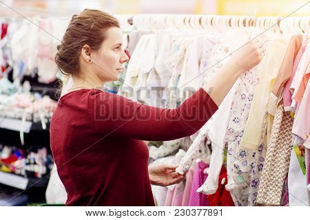 Young Attractive Girl Is Choosing Clothes In The Mall. Try On Clothes On The Hanger In The Store. Sh