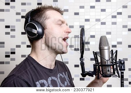 A Young Guy Singer And Rock Musician Sings In A Studio Condenser Microphone In Headphones In A Recor
