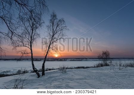The Setting Sun On A Frosty Evening Over A Snow-covered Valley