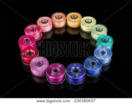 Plastic Sewing Machine Bobbins With Colorful Threads On Black Background