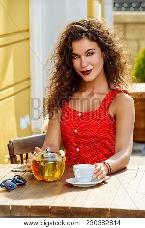 Happy smiling girl is sitting at a table in a café. Sunny summer day.
