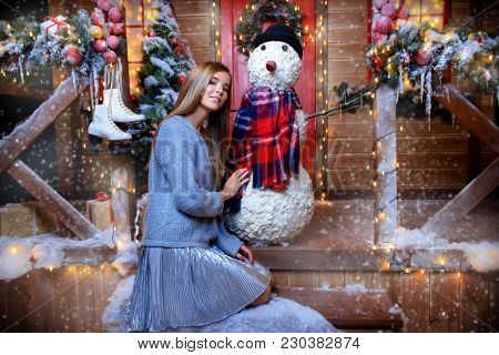 Happy girl in a warm winter clothes and earmuffs poses with snowman near the house decorated for Christmas. Time for miracles. Merry Christmas and Happy New Year.