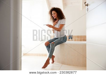 Woman In Bathroom Celebrates Positive Home Pregnancy Test Result