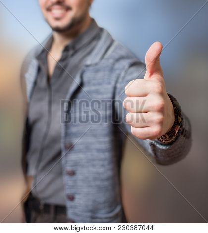 Man's Thumb In A Symbolic Approval Gesture Thumbs Up, Blurred Face