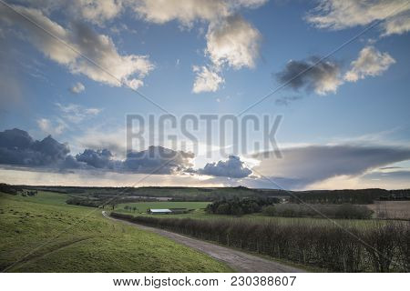 Beautiful Stormy Moody Cloudy Sky Over English Countryside Landscape At Dusk
