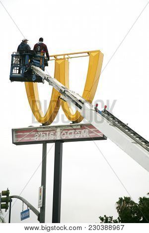 Lynwood California - 3-9-2018:  Workmen use a crane to remove and replace the iconic McDonalds Restaurant after International Women's Day. The M design was turned upside down to read as W for the Day