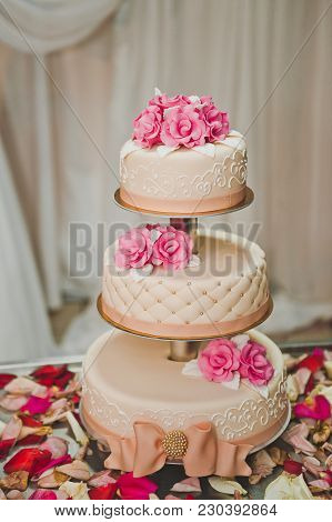 A Three Tiered Cake With Pink Flowers.