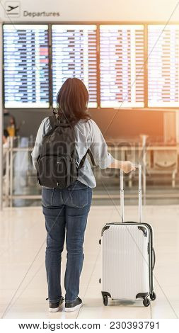 Passenger Traveling With Luggage And Backpack At The Flight Information Board In Airport Terminal Wa
