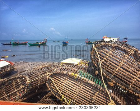 Fishing Traps Waiting To Be Cast Off On The Shore Of Kep, Cambodia Near Kampot.  The Market Behind I